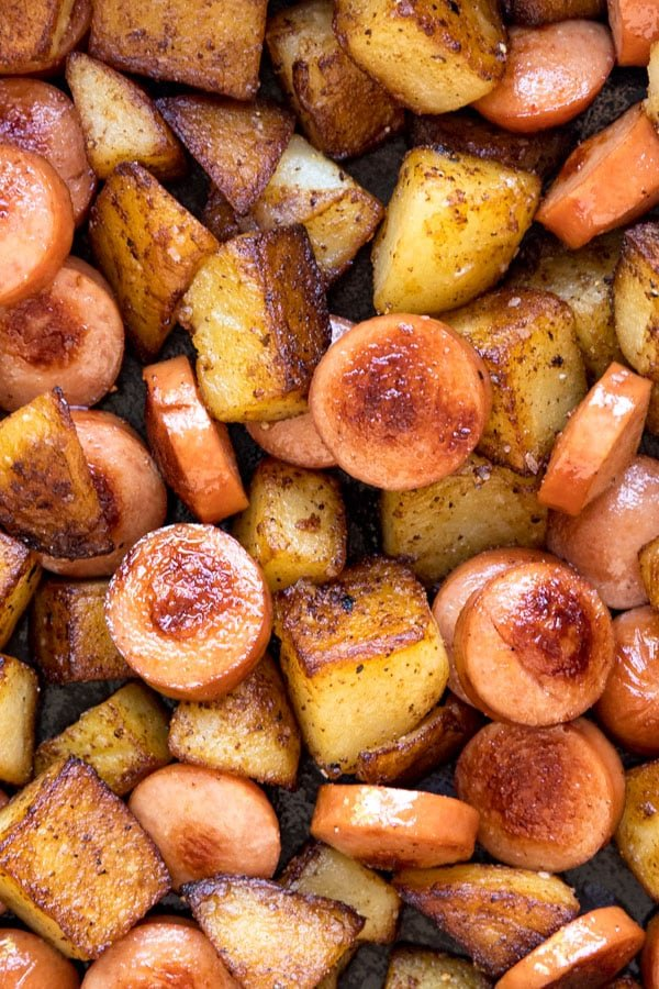 An overhead image of cut up hot dogs and potatoes that have been cooked.
