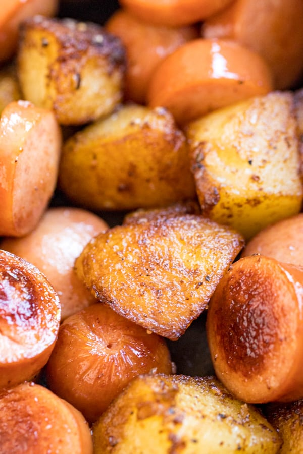 A close up image focusing on a fried potato in a pan with potatoes and hot dogs.