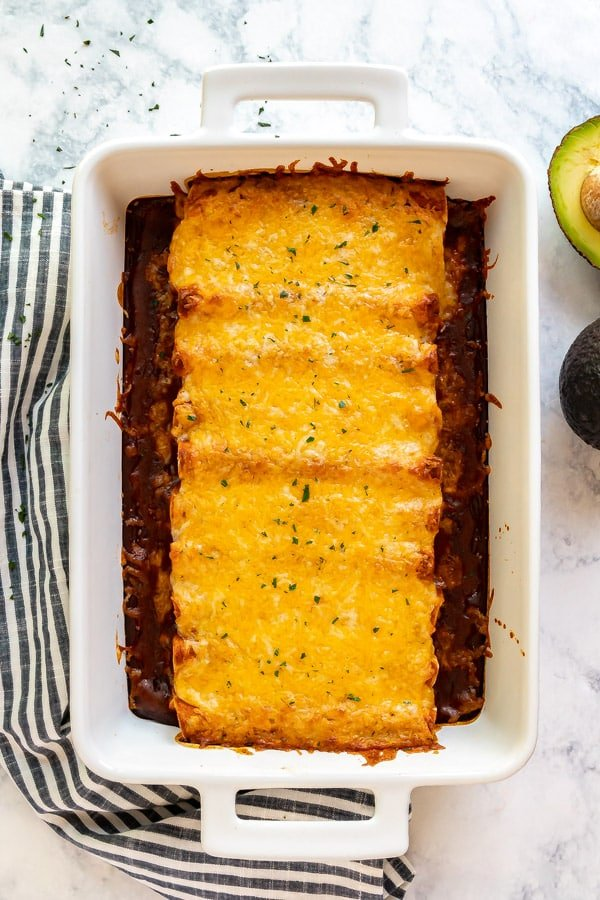 An overhead mage of a pan of enchiladas with a black and white striped towel on the left side and an avocado cut in half on the right side.