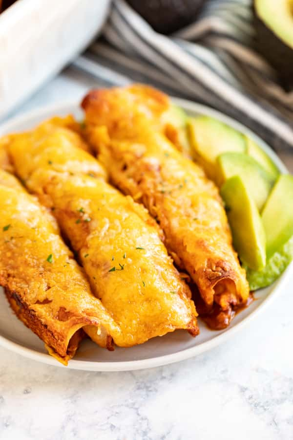 A close up image of 3 chicken enchiladas on a plate with sliced avocado next to them.