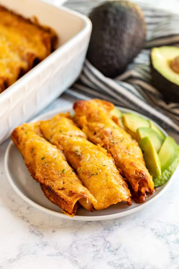 3 enchiladas on a plate with sliced avocado.