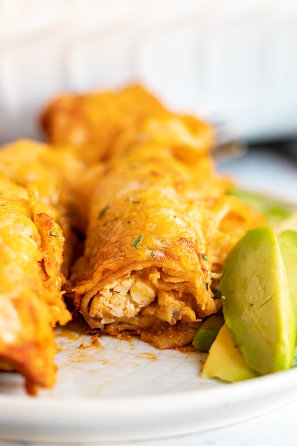 A straight-on image of an enchilada on a plate that's been cut in half revealing the chicken inside of the enchilada.
