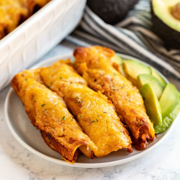These Easy Chicken Enchiladas recipe may not be the most authentic, but they are seriously delicious and come together really quickly! They're cheesy with shredded chicken and an easy red sauce- the perfect weeknight meal!