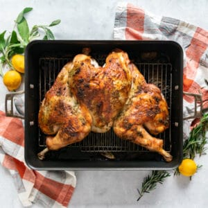 An overhead image of a roasted spatchcocked turkey in a roasting pan surrounded by fresh herbs and lemons and orange and grey plaid napkins.