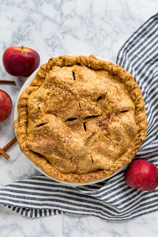 An overhead image of the whole pie with apples around it.