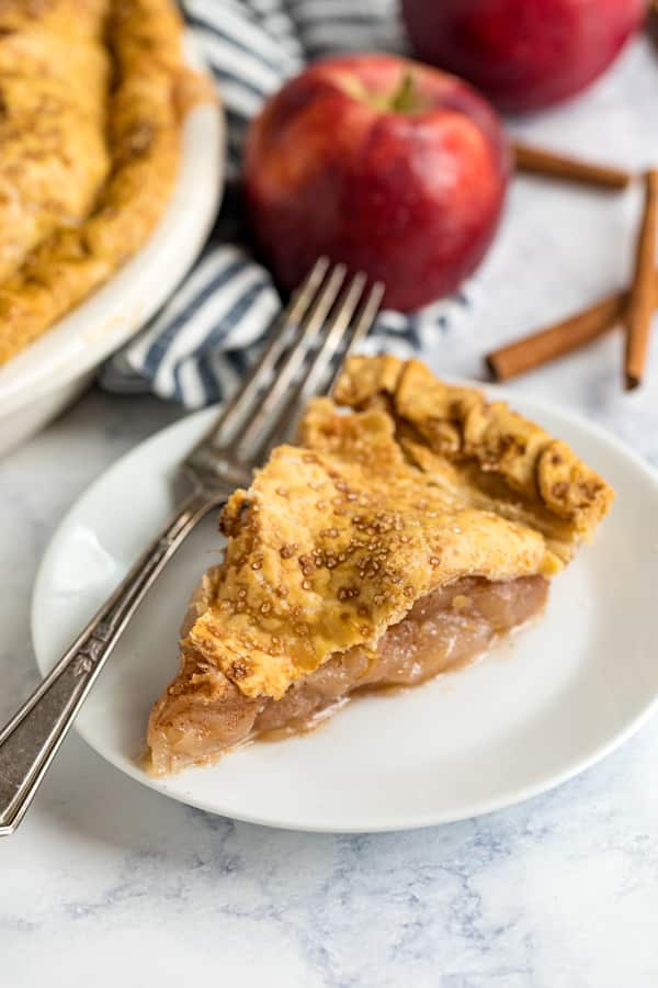 A slice of apple pie on a white plate with a fork on it and some apples in the background..