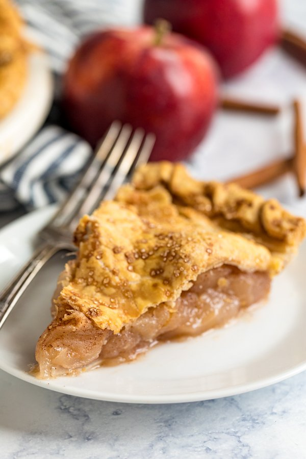 A close up of a slice of apple pie on a white plate with a fork in the background.