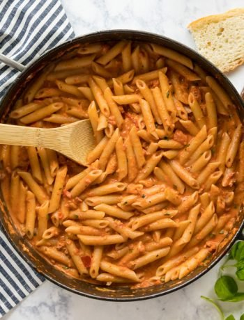 A square overhead image of a pan of penne vodka with a spoon in it surrounded by bread, basil and a striped towel.