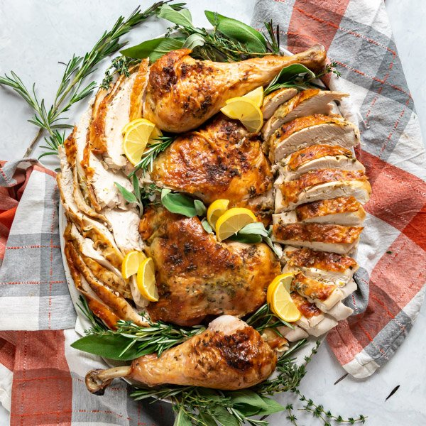 An overhead image of a carved turkey arranged on a serving platter with fresh herbs and lemons surrounding it.