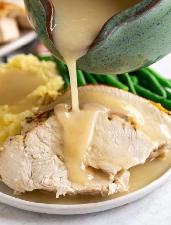 A square image of gravy being poured onto turkey breast slices on a thanksgiving plate.