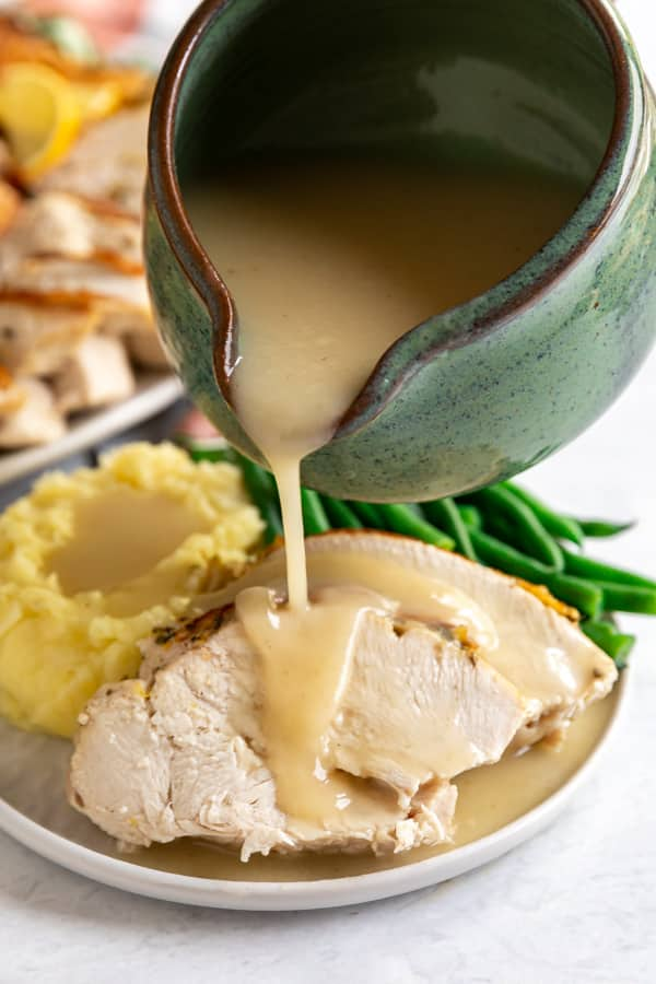 A green gravy boat pouring the best turkey gravy on turkey breast on a thanksgiving dinner plate