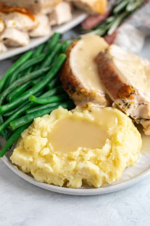 A thanksgiving plate with mashed potatoes and gravy up front and turkey and green beans in the back of it.