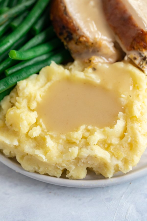 A close up of mashed potatoes on a grey plate with easy turkey gravy in the middle of them and greenbeans on the plate in the background.