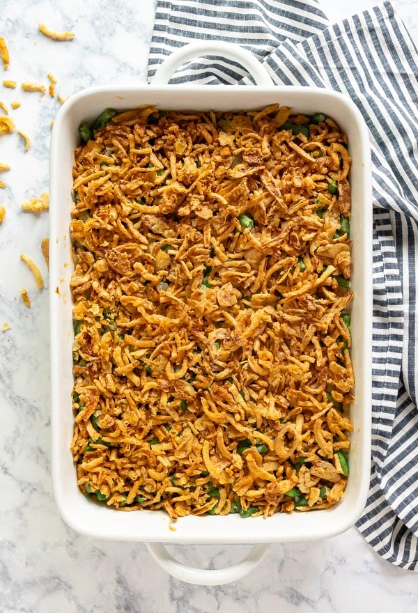 An overhead image of a pan of green bean casserole with french fried oniond on the top and around the pan and a black and white stripped towel to the right of it.