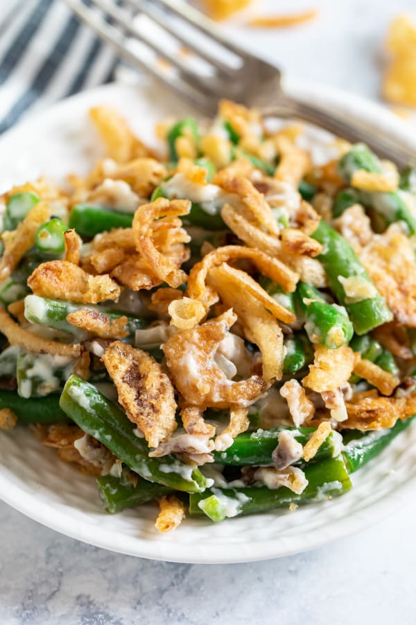 A close up image of a white plate of green bean casserole with a fork on the back of it.
