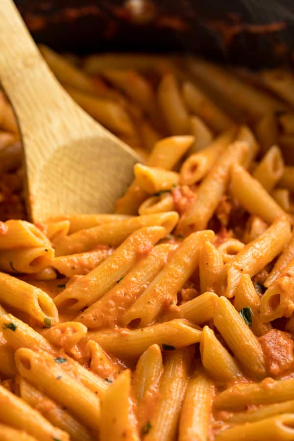 A close up of penne vodka sauce in a pan with a wooden spoon in it.