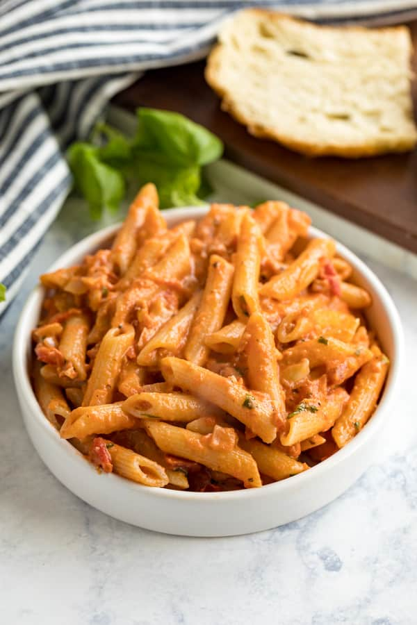 A close up image of a plate of penne ala vdka with bread and basil behind it.