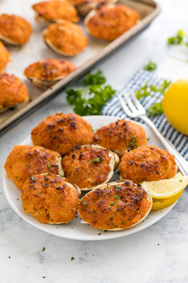 A plate of baked clams casino with lemons and parsley behind it and a pan with more clams behind it.