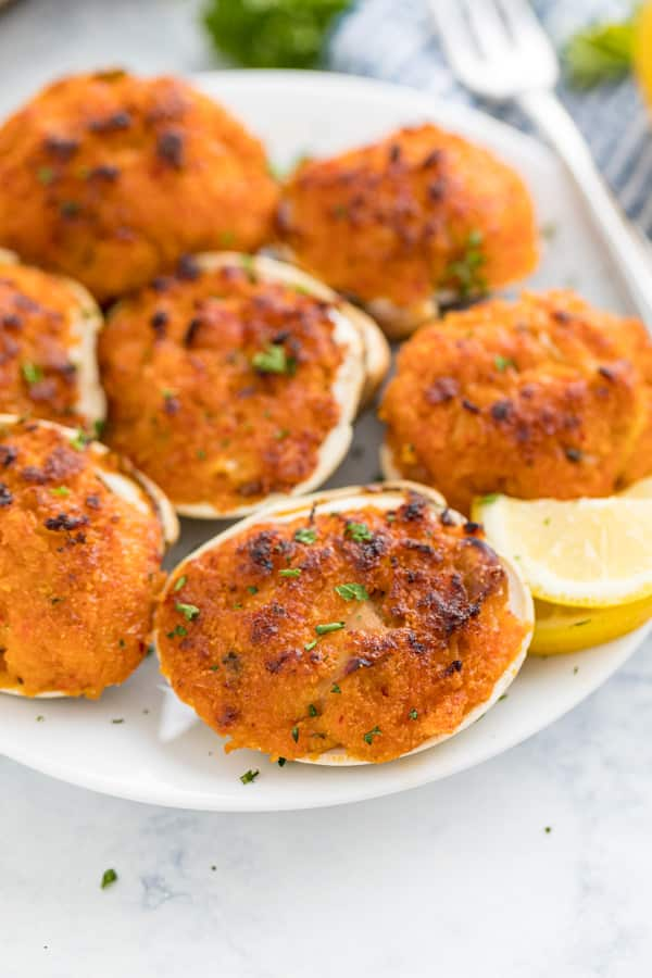 A close up image of clams casino on a white plate with a lemon wedge on the plate.