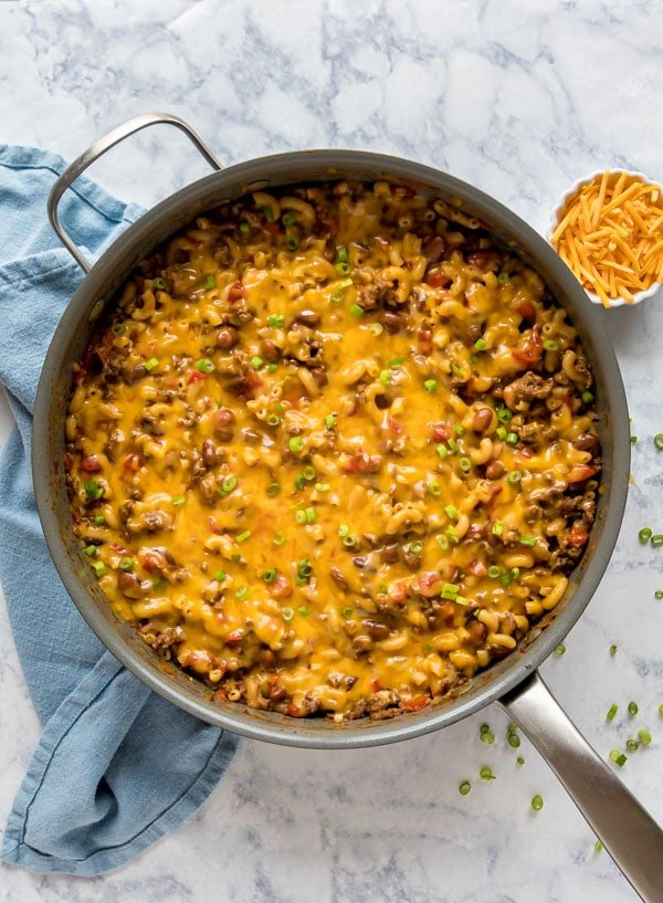 An overhead image of a pan of chili mac with a blue towel next to it and a small white bowl of shredded cheddar cheese.