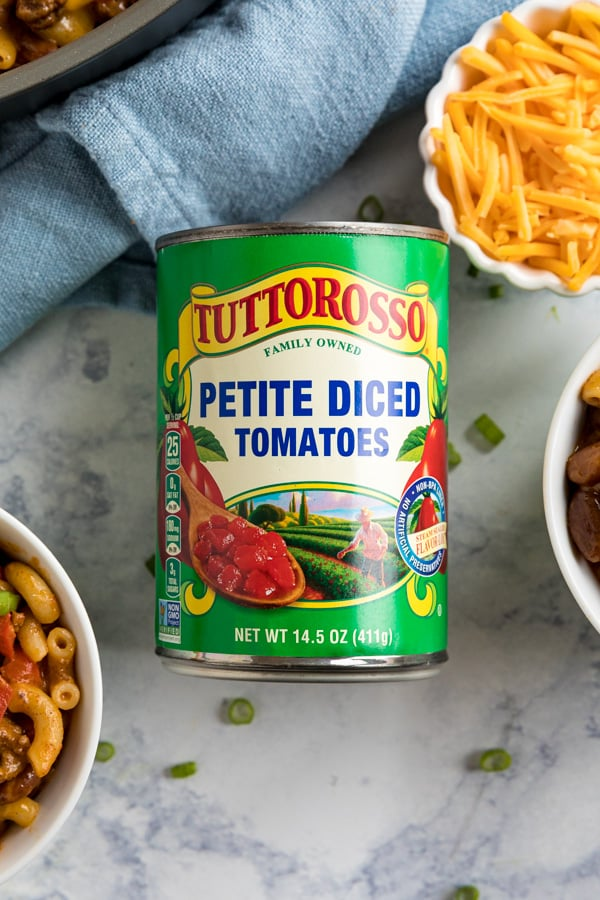 An overhead image of a can of Tuttorosso tomatoes with bowls of chili mac on either side of it , a blue towel around the top and a bowl of shredded cheese.