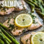 Three pieces of Salmon lined up on the diagonal on a sheet pan with Asparagus on either side of it, the center piece of salmon is in focus and everything surrounding it is blurry. Each piece of fish has a lemon round on it.