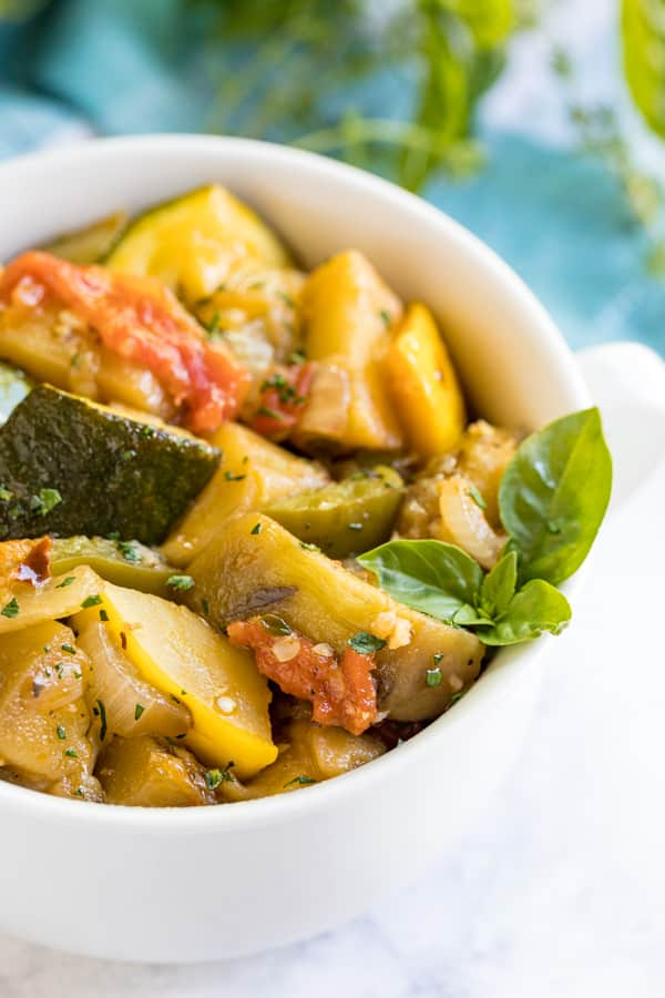 A close up featuring the side of a white bowl of Ratatouille, zoomed in on the chunks of vegetables and sprig of fresh basil.