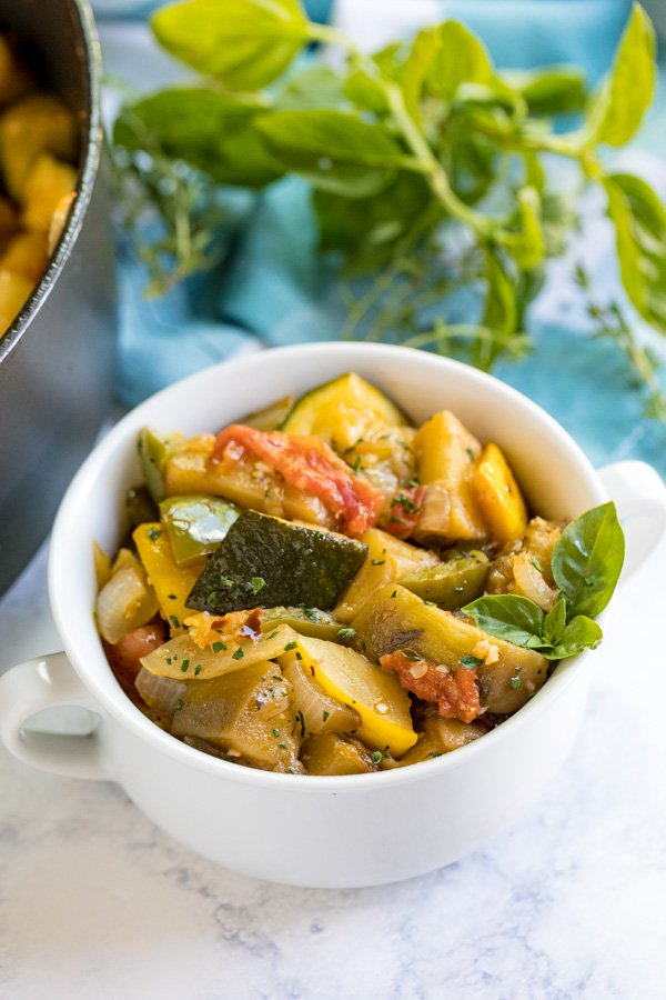 A side image of a bowl of Ratatouille with a sprig of fresh basil in it and a blue and white napkin and fresh herbs behind it.