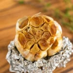 A close up image of a bulb of roasted garlic revealing it inside on top of some tin foil on a cutting board.