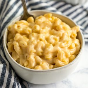 A square image of a bowl of creamy mac and cheese with a striped naplin and shredded cheese behind it.