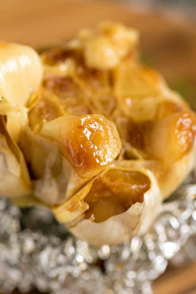 A close up image of a piece of roasted garlic thats slightly squeezed out of the bulb revealing the texture of the garlic.