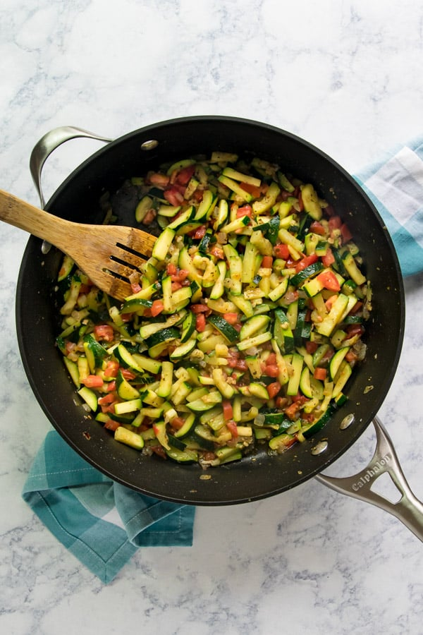 An overhead image of Sautéed Zucchini and Tomatoes in a sauté pan with a wooden spoon in it on top of a blue and white checked napkin.