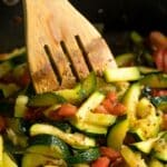 Sautéed Zucchini and Tomatoes in a sauté pan with a wooden spoon in it.
