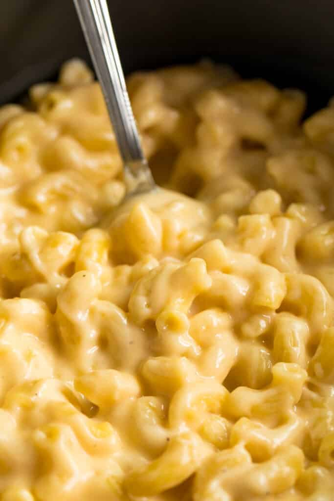 A close up of a spoon inside of pot of macaroni and cheese.
