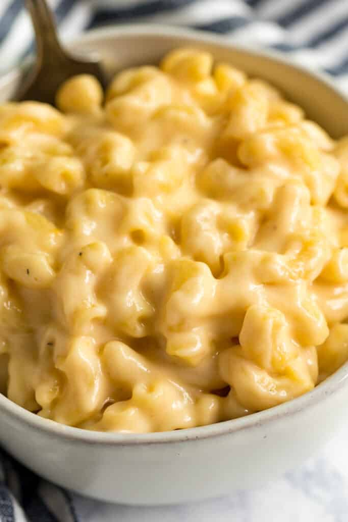 A close up of the creamy macaroni and cheese in a bowl with a soon sticking out of the back of the bowl.