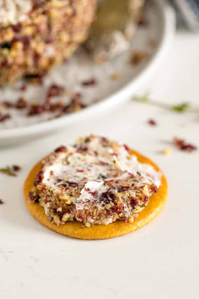 A cracker with some of the cheese mixture spread onto it with the cheeseball behind it.