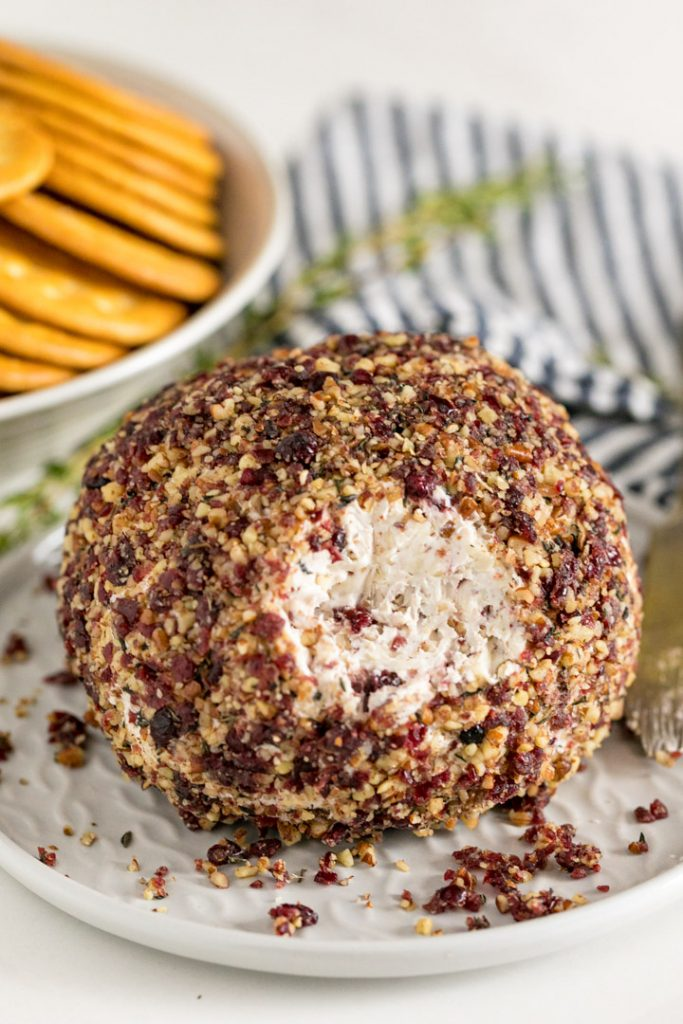 A cheese ball with some pulled off the front exposing the creamy inside of it with crackers and a striped napkin behind it.